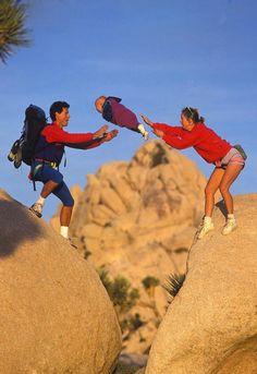 Deux parents et leur bébé font de la randonnée. Pour passer un obstacle, la maman jette son bébé au dessus du vide, dans les bras du papa.