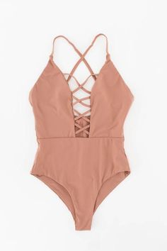Seamless one piece swimsuit with a caged front in dusty rose. Cheeky fit with high leg cut sides. Open square back with adjustable straps. Made and manufactured