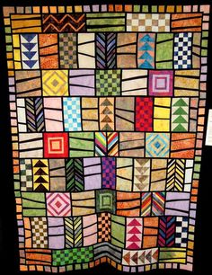 """Quodlibet"" by Constance Clark, 2012 - Assorted blocks framed in irregular black sashing to create stained glass look in patchwork quilt - on Quilt Inspiration"