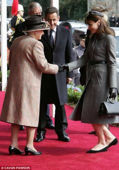 French first lady, CarlaBruni-Sarkozy curtsies as she meets the Queen