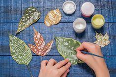 Dipingere sulle foglie: possiamo dipingerle con una base di colore neutro, e poi con il bianco realizzare decori...