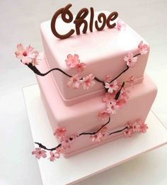 Two tiers covered in fondant. Gumpaste hand made cherryblossom flowers and name.
