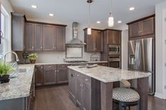 Kitchen: Stained hardwood floors, cabinets, and island, granite counters, stainless steel appliances, natural light