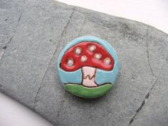 This ceramic pottery magnet has been handmade from white earthenware clay. I have hand drawn a fairy mushroom design into the surface before painting with colourful underglaze pigments. https://www.etsy.com/uk/listing/161438513/handmade-ceramic-pottery-faery-mushroom
