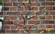 """Von groß bis klein, lackiert bis rostfarben – Vogelvolieren sind in der Dekowelt gerade äußerst beliebt und auch zwischen Garten-Accessoires zahlreich zu finden. Das Wandbild """"Voliera"""" ist aus Eisen gefertigt. Für eine höhere Witterungsbeständigkeit wurde es sogar zweimal lackiert."""