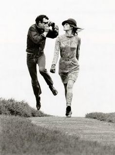 A guy takes photos of a woman walking.  Helmut Newton Photography - capturing a moment