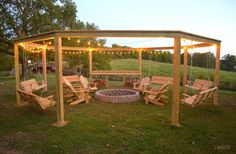 If you're looking for the ultimate summer project, this DIY pergola, complete with swinging wooden benches and a fire pit, looks pretty amazing!
