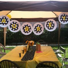 banner: made with paper plates, glue, yellow poster board, stencils, black and white polka dot wrapping paper. Tied up with balloon ribbon.
