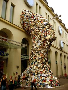 Artist Alicia Martin's tornado of books shoot out a window like a burst of water from a giant hose. The Spain-based artist's sculptural installation at Casa de America, Madrid depicts a cavalcade of books streaming out of the side of a building.