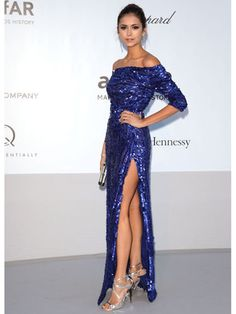 Nina is wearing a cobalt blue sequin long sleeve off shoulder Elie Saab gown with a thigh high side slit paired with silver Jimmy Choo cutout heeled sandals. I adore the cobalt blue! The sequins with the off shoulder and thigh high slit is sexy and glam! Work it, Nina!