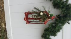 This is one of the matching red lanterns I designed for our white, vinyl fence.  We hang garland on the pickets on top.  Since hubby wouldn't drill holes in the fence, I just leaned shepard's hooks up on the back side of the fence so the hook-part came through one of the pickets & hung my lantern on the front-side of the fence!  I have battery-operated candles in each lantern.