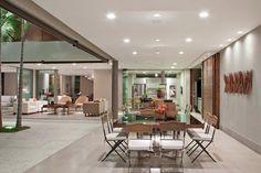 """A área de lazer é o ponto principal da casa. Na varanda em """"L"""", as profissionais posicionaram o espaço gourmet junto à cozinha do chef, setorizados apenas por lâminas de vidro."""