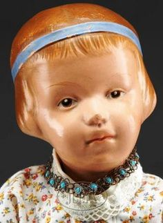 SCHOENHUT GIRL WITH CARVED HAIR. Desirable child with closed pouty mouth, intaglio brown painted eyes, with separately molded eyelids, deep carving in hair showing comb marks, with a blue ribbon band tied in a bow in the back. Appropriately redressed in 1910-style floral print cotton, wearing newer leather shoes and socks.