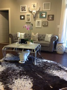 """In love with my new modern, purple & gray living room! The inspiration to this room was the gray, tufted sofa from Wayfair.com and the metallic bulls skull from Z Gallerie! I primed, hand painted an old brown tiled table with Rustoleum Metallic Spray Paint. Brown, Gray & White Cowhide Rawhide Rug from At Home. ($100 less than Z Gallerie) Wall Gallery includes an eye chart that reads """" ANDREW AND CHRISTINA EST. 9*10*11, Purple Petals from My Wedding Bouquet, Marines tribute cabinet with…"""