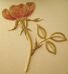Goldwork rose. The petals of the flower are worked in Or Nué and surrounded by pearl purl.