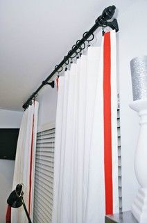 Adding orange-red trim to Cameron cotton panels from Pottery Barn gave these curtains a brand-new look. I often use those panels because they have a sturdy weight but cost just $25 each.   Spray painting the existing curtain rod and using black rings upgraded the custom look even more.