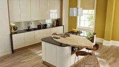Barra integrada en la isla de cocina, en madera, un material muy apropiado por su facilidad para combinar con cualquier color o estilo y desarrollar formas curvas.