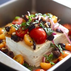 This baked feta is topped with tomatoes, olives, red onion and fresh herbs. Serve with pita chips! It's great for parties.