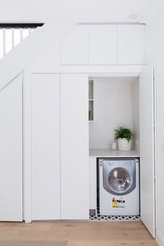 Laundry before and after: Dreamy Euro style laundry behind pocket doors Laundry In Kitchen, Laundry Cupboard, Tiny Laundry Rooms, Laundry Room Remodel, Door Under Stairs, Space Under Stairs, European Laundry, Hidden Laundry, Compact Laundry