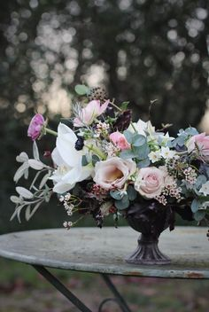 Pale pinks and white flowers in a winter wedding table flower arrangement by Amber (from Little Thatch Florist in Somerset) made at a Jennifer Pinder floral styling workshop. Jennifer Pinder specialises in wedding flowers and classes for both hobbyists and florists. In this arrangement (made in January so perfect for a winter wedding) Amber has used white 'Christmas' amaryllis, qicksand roses, ranunculus, waxflower, narcissi and blush pink spray roses.