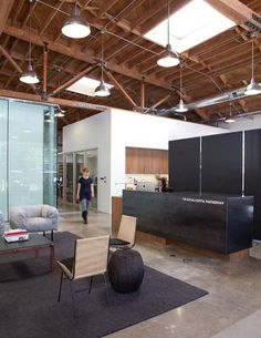 Social + Capital office design in Palo Alto | Reception desk & waiting area with exposed rafters and freestanding office pods