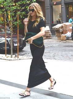 Height of chic: Rosie HUntington-Whiteley donned a simple long black frock as she arrived at her hotel in New York City on Thursday. Natural beauty: Rosie wore her blonde hair waves and kept her make-up fresh
