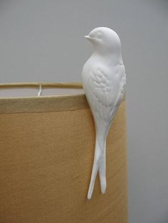 Lovely porcelain swallows! These beautiful handmade porcelain swallows are designed to perch atop a lampshade, turning any lampshade into a real design feature! They also cast a pleasing bird shaped shadow on a near wall. They can also clip onto the top of vases or glasses etc. or anywhere else you can find that works! Great as gifts or decorative accessories for your home.Porcelain!Approx: 12cm.