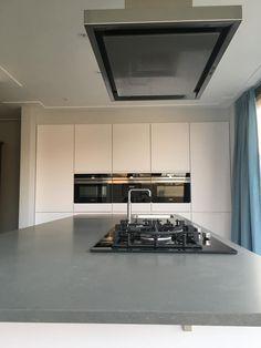 Referentie Wildhagen   Betonnen keukenblad met kookplaat en hoogglanzende keukenwand met inbouwapparatuur. https://www.facebook.com/wildhagen.nl/posts/775334129238322 #designkeukens