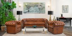 English Antique Leather Chesterfield Sofa & Club Chairs... with mid-century modern table, Murano glass lighting & accessories, and contemporary art.