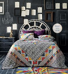 chalkboard wall, bed, empty frames, book pages, colorful rug, patterned duvet...love it all <3