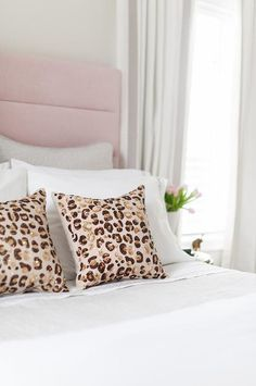 Brown and pink animal print pillows are layered in front of white and gray shams positioned against a pink channel tufted headboard placed beside a window dressed in gray border curtains.