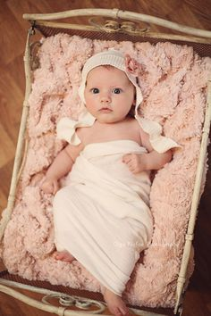 11-week-old baby girl in antique cot wearing white flower bonnet, unique fine art baby portraits by Olga Klofac Professional Baby & Child Photographer Charlestown Mayo   www.mayophotographer.ie
