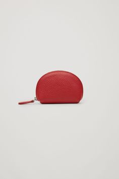 A rounded, structured shape, this purse is made from a soft leather with a grained finish. Designed with a single main compartment and lined with a cotton twill, it is secured with a chunky metal zip.