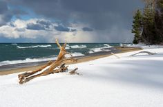 A worn piece of driftwood sits along a snowy Lake Superior shoreline at Pictured Rocks. Munising, MI