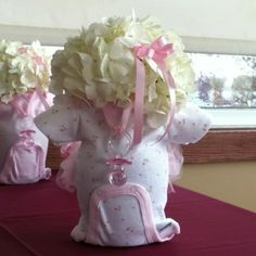 This is adorable!  Looks like the onesie is stuffed with some sort of batting, then a hydrangea is inserted.  I will have to figure out how to do this...