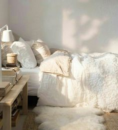 the use of different textures and soft white colour scheme, in the bedding and area rug are very inviting and warm.