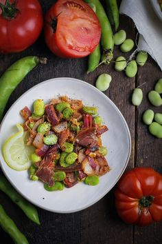 A warm tapas dish of Spanish-style fava beans with tomatoes and jamón