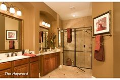 Custom tile and glass frame the walk-in shower, Dual recessed sinks with symmetrical mirrors and light fixtures balance this Master Bath. David Weekley Homes, The Hayword Model, Waterhaven Community, near Houston.