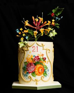 21st birthday cake, inspired by Russian Zhostovo trays.  The central panel is handpainted, and is framed by gold royal icing.  On the top is a floral spray incorporating honeysuckle and holly, with small blossoms mirroring those on the painting.  This is my first double-barrel cake and also my first attempt at panelling with fondant for covering the cake.  Hope you like it!
