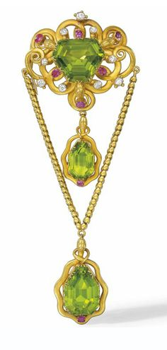 A MID-19TH CENTURY PERIDOT, RUBY AND DIAMOND BROOCH  The openwork panel centred by a kite shaped fancy-cut peridot to an old-cut diamond and ruby border, raised in a scrolling entwined snake motif surround, suspending two simialarly designed pear shaped peridot drop pendants, circa 1860, 13.8cm long