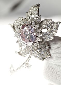 The Queen's Williamson Diamond Brooch contains what is thought to be the finest pink diamond ever discovered. The petals, stalk and the leaves of this brooch are set with 170 small brilliant-cut diamonds, 12 baguette-cut diamonds and 21 marquise diamonds. Cartier, London, 1953, diamonds, platinum, 10 × 5.5 cm http://www.royalcollection.org.uk/exhibitions/diamonds-a-jubilee-celebration/the-queens-williamson-diamond-brooch