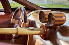 The two gauges pictured here are a speedometer and tachometer, held inside cups made of cherry wood. Mr. Harmon rotated the grain in the wood to create the striped look. The baseball bat-looking thing is part of the manual gear shifter.