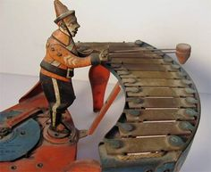 """Made in the 1930s by Wolverine Manufacturing Company of Pennsylvania, this vintage musical automaton toy plays the xylophone. The tune it plays is """"programmed"""" on the profile of a cam measuring about 3"""" in diameter. By changing the came, the little figure will play any one of six songs:1. The Farmer in the Dell2. Yankee Doodle3. My Old Kentucky Home4. Sidewalks of New York5. Silent Night6. Listen to the Mocking Bird"""