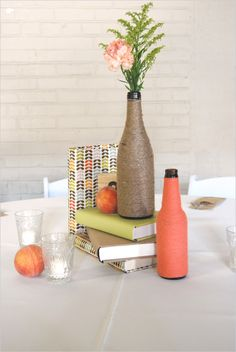 yarn wrapped bottles and covered books for table decor