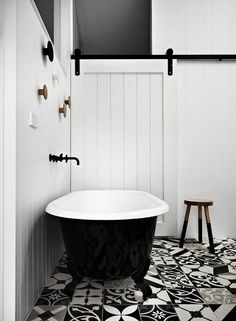 Black clawfoot bathtub, black and white morrocan tiles