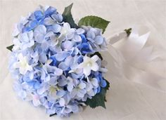Perhaps use blue hydrangea small bouqets for your Bridesmaids with hints of white in to compliment the Bride bouquet  Blue Hydrangeas Bouquet. Lilies of the Valley and Stephanotis.