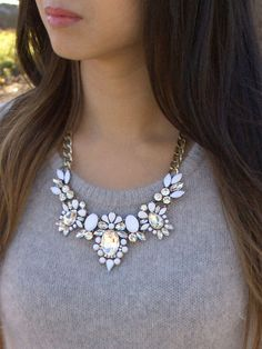 A stunning floral motif bib necklace with a neutral, eye-catching palette. The ultra-white cabochon and faceted gems contrast beautifully with the clear, crystal sparkle.