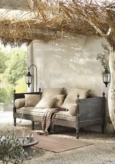 rustic Mediterranean outdoor retreat - daybed on a cobbled floor, hanging lanterns, vine arbour roof