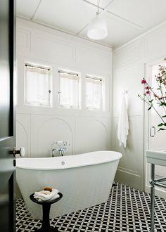 white soaking tub with black + white tile floor #bathroom