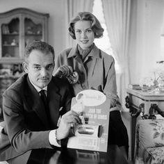 """Original caption: Rainier and Grace  Joins March of Dimes. New York: Because they will not be in the United  States next January when the March of Dimes drive is opened, Prince  Rainier III and Princess Grace of Monaco this week made advance  contributions to the 1957 March of Dimes campaign. They are shown  depositing their gift in miniature """"iron lung"""" coin collector, symbol of  tens of thousands for whom the Salk Polio Vaccine comes to late. This  was the first of more than a ..."""